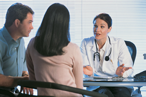 Man and woman sitting at desk with healthcare provider discussing information in medical chart.