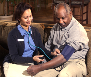 Healthcare provider taking man's blood pressure at home.