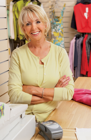 Woman standing behind cash register in clothing store.