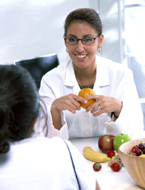 Healthcare provider talking to woman at table. Bowl of fresh fruit is on table.