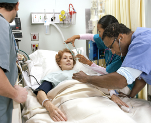 Three health care providers around hospital bed attending to older woman.