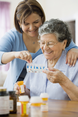 Woman helping senior woman with medication organizer.