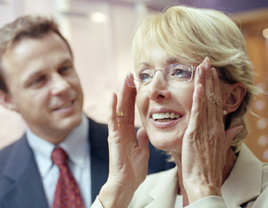 Woman putting on glasses with man in background.