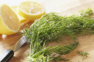 Sliced lemons and bundle of herbs with knife on cutting board.