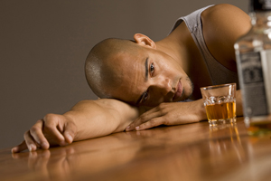Drunk male, lying  on table staring at empty bottle of alcohol and glass of alcohol.