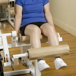 Woman doing leg extensions on exercise equipment.