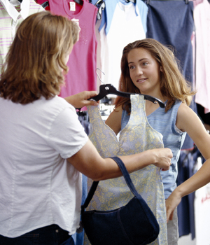 Woman and teen girl shopping for clothes.