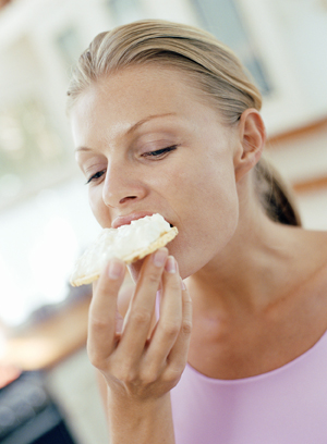 Woman eating cottage cheese on cracker.
