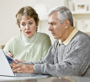 Senior couple using laptop in living room.