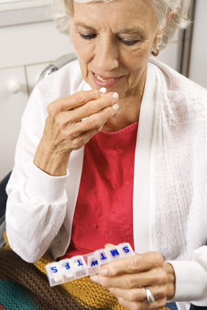 Elderly woman with pill box.