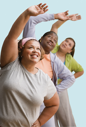 Three overweight women doing side bends exercises.