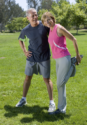 Mature couple exercising in park, woman stretching.