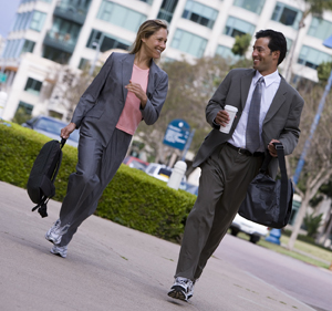 Man and woman dressed in business attire and athletic shoes walking briskly on pavement in city, smiling.