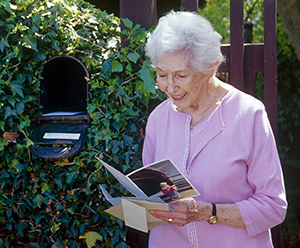 Senior woman standing at mailbox in front of house.
