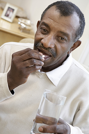 Close up of senior man taking a pill with a glass of water.