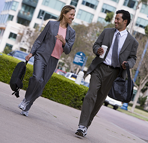 Businessman and businesswoman walking on pavement in city, wearing athletic shoes, smiling.