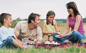 Father, mother, son and daughter having a picnic on a blanket outdoors.