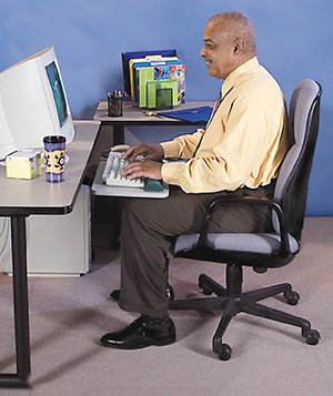Mature man sitting at desk infront of computer in correct ergonomic position.