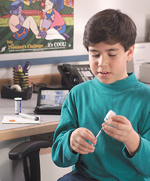 Boy filling syringe with insulin.