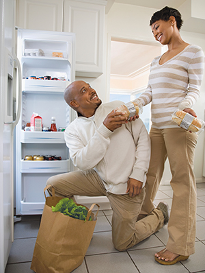 Couple in kitchen, putting groceries in refrigerator.