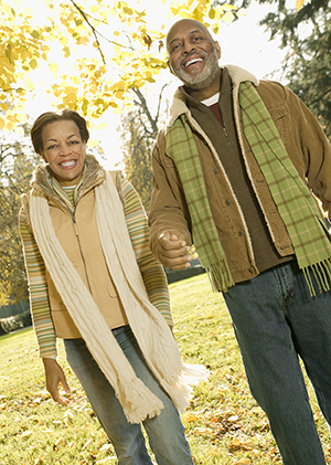 Middle-aged couple walking in a park on a cold autumn day.
