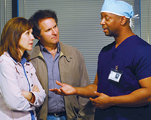 Healthcare provider in surgical scrubs talking to man and woman.