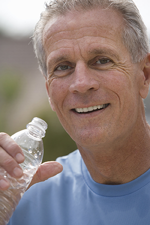 Active senior man drinking water from plastic bottle.