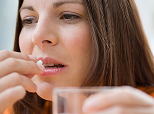 Woman taking pill with glass of water.