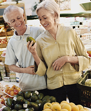 Man and woman shopping in produce section of grocery store.