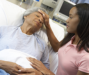 Young woman resting hand on senior woman's forehead in hospital bed.
