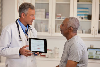 Doctor shows ECG results to patient using an electronic tablet