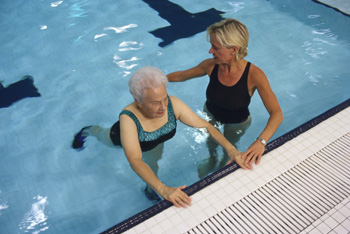 Two women exercising in shallow end of swimming pool.