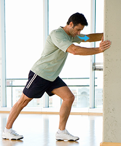 Man doing calf stretch exercise.