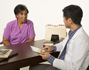 Woman sitting at desk talking to doctor.