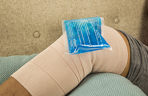 Closeup of elevated knee with bandage and ice pack.