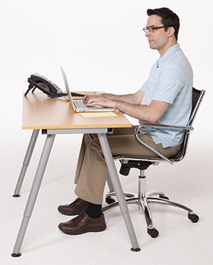 Man sitting at desk with correct posture.