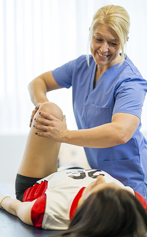 Physical therapist working with woman's knee.