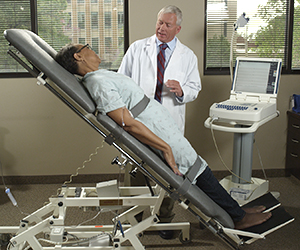 Healthcare provider monitoring patient during tilt table test.