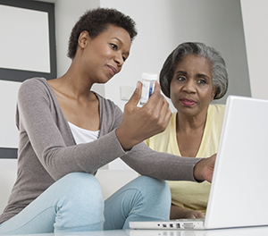 Two women looking at medication bottle and laptop.
