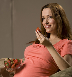 Pregnant woman eating strawberries.