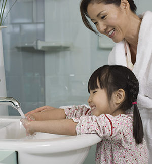 Woman watching girl wash hands in sink.