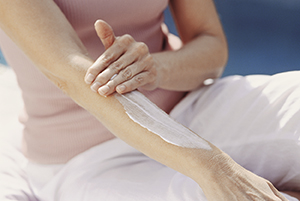 Woman smoothing lotion on arm.
