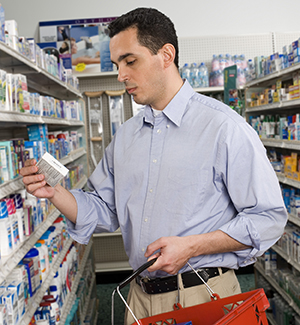 Man reading over-the-counter medication box in pharmacy.