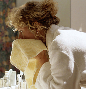 Woman drying face with towel.