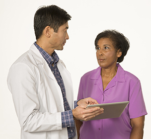 Doctor and patient talking, doctor holding tablet.