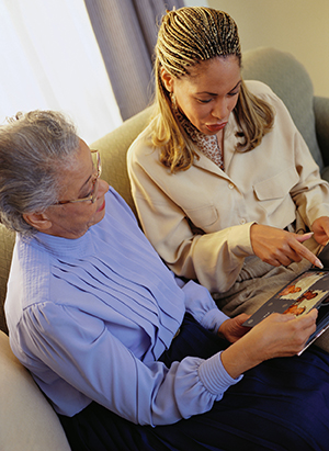 Two women looking at photo album.