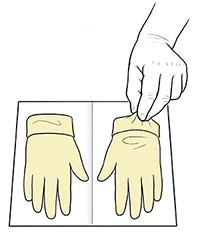 Hand picking up glove from opened sterile glove packet.