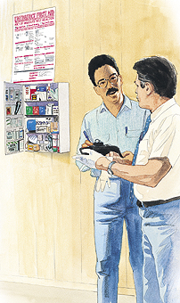 Two men looking at safety equipment in cabinet.