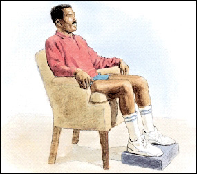 Image of man in chair sitting with legs up on a footrest